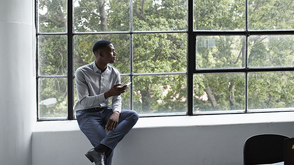 young man sitting in front of window