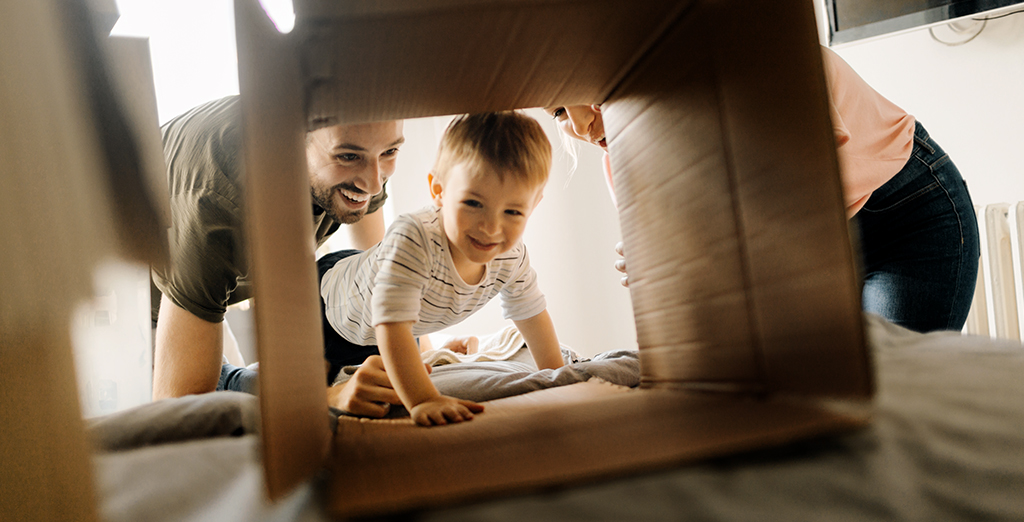 Parents playing with toddler and cardboard box