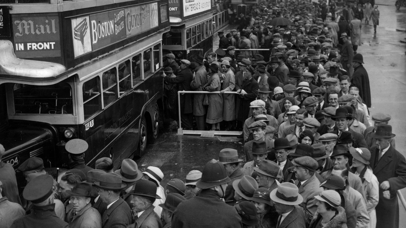 Crowds at Morden wait to board buses for the Epsom Derby in 1935