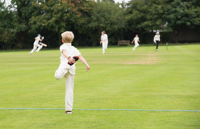 Child in cricket whites stretching in the outfield during a match