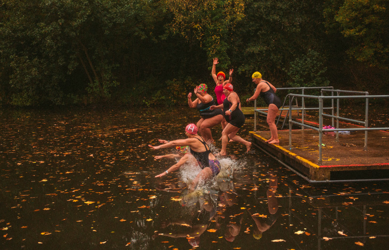 Six older women in swimming kits bravely jumping into a cold autumn pond
