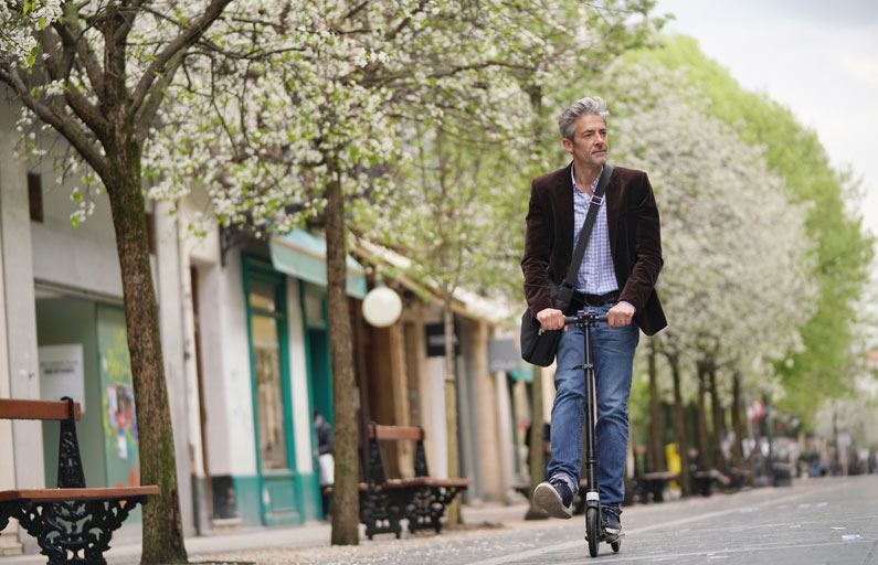 Middle-aged man on a scooter travels down a tree-lined street