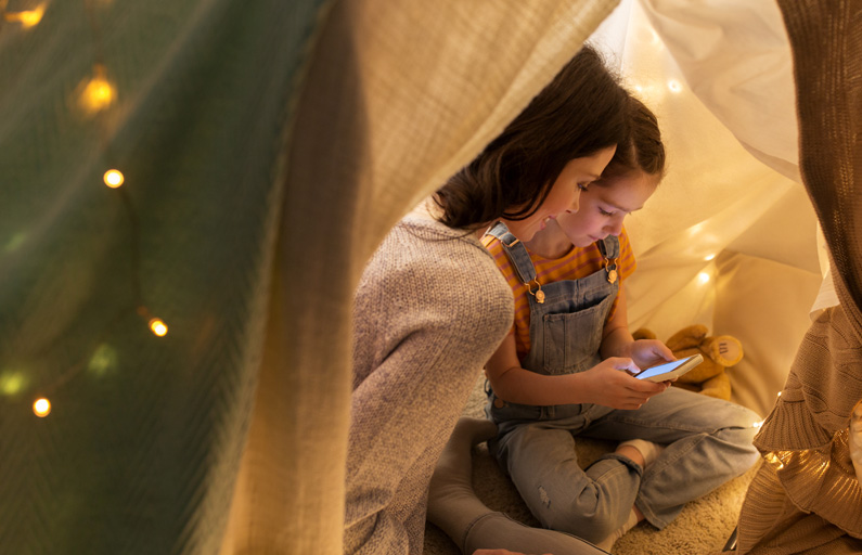 Mother and daughter cuddle up in a pillow fort