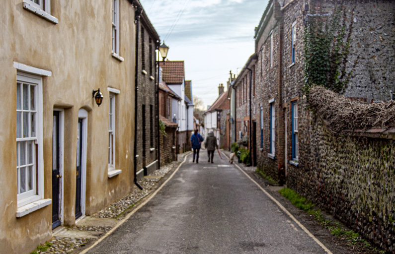A couple with a dog walk down a narrow British town street