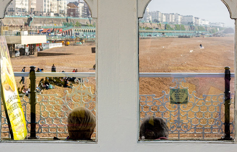 Elderly couple look out over Brighton beach from the pier