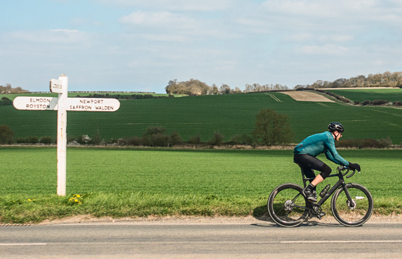 Cyclist passing roadsign in English countryside