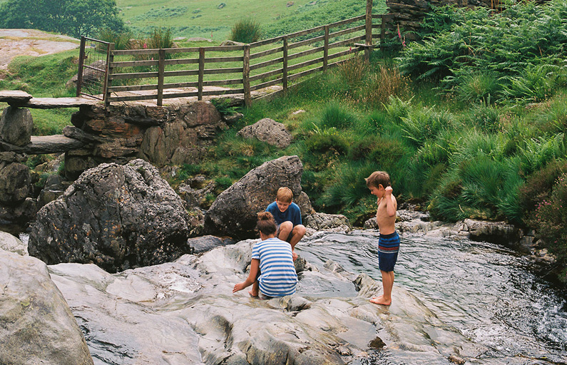 Three young children playing in a local riverbed