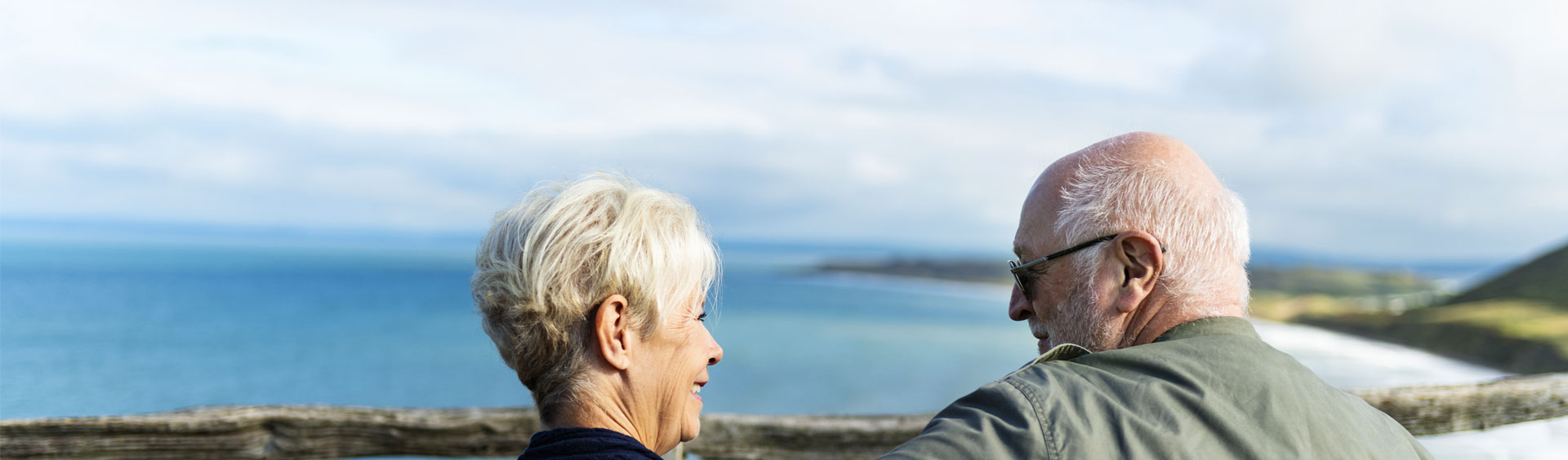 Elderly couple smile at each other overlooking the ocean