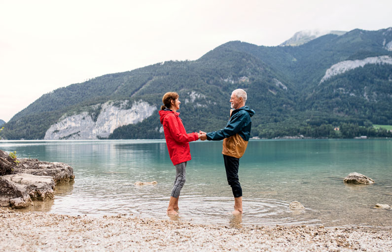 A couple standing in the shallows of a lake holding hands