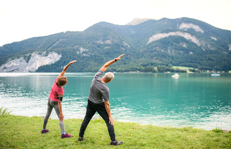 A couple stretching together beside a lake