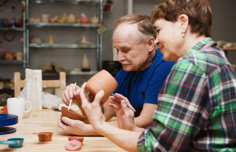 Middle-aged couple paint pottery together