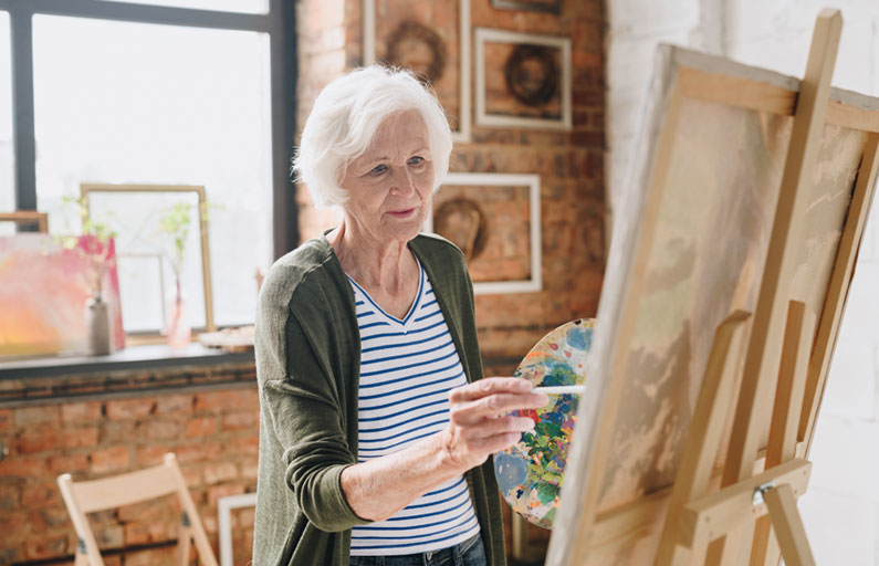 Elderly woman paints on a canvas in a light-filled room