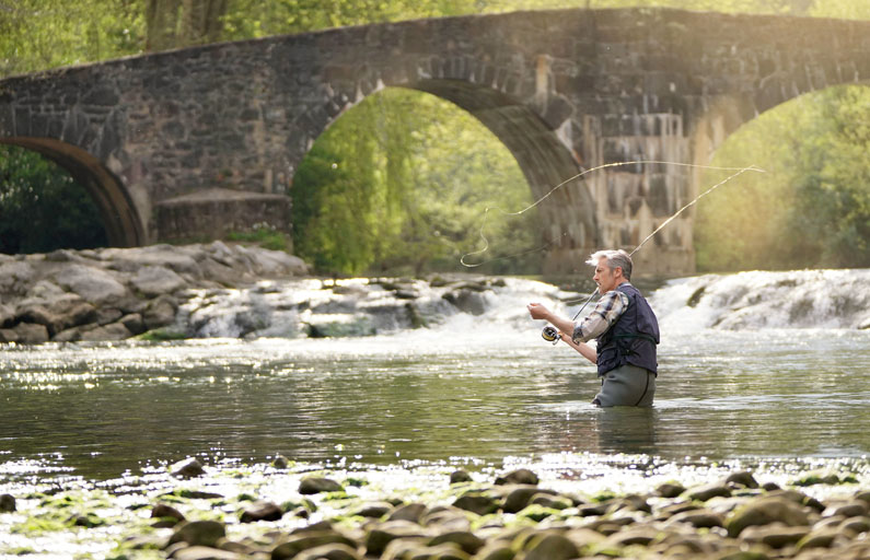Middle-aged man fly fishing in a river