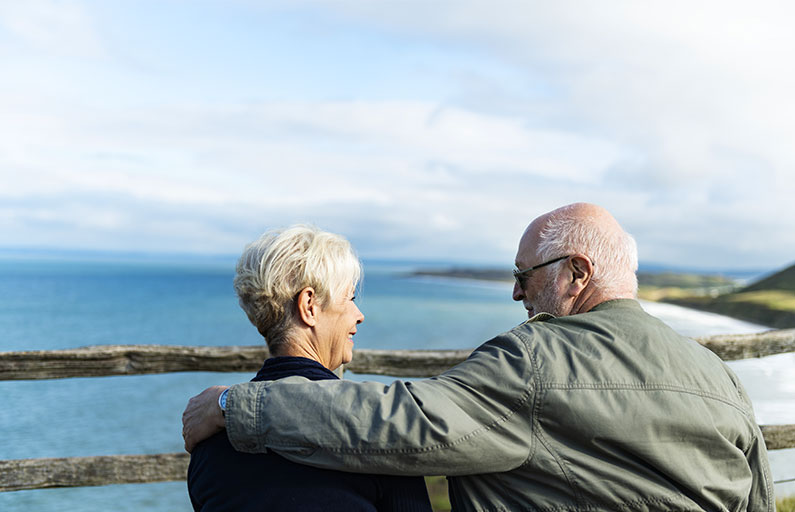 Elderly couple smiling at each other on a windy coastal lookout