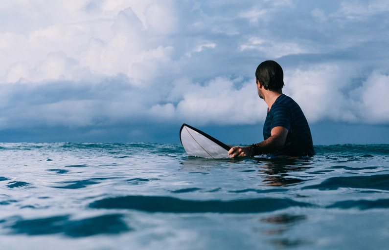 Surfer in the ocean looks back at next wave