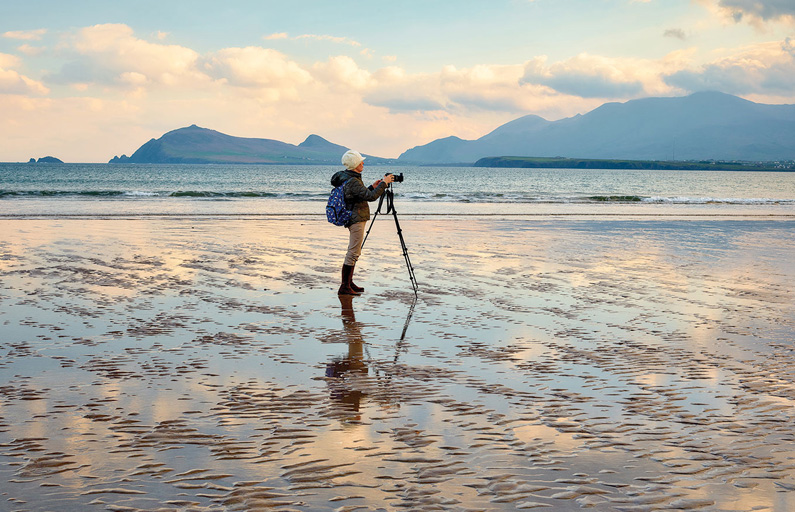 Photographer with a tripod capturing a still beach at sunset