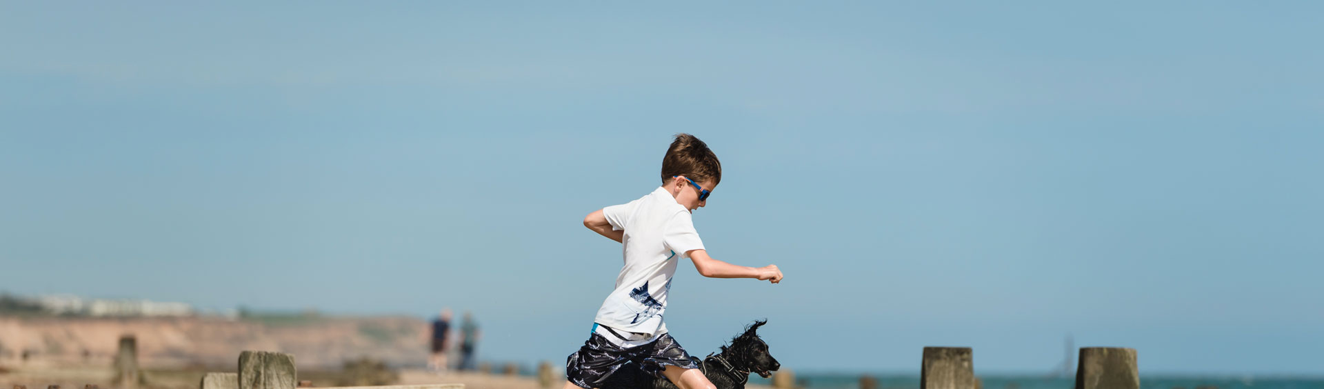 Young boy with sunglasses mid-leap