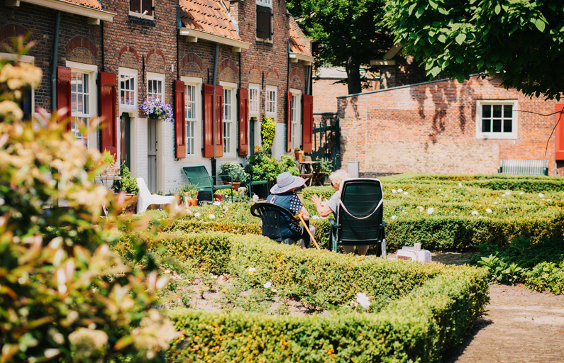 Two old ladies seated swap stories in the garden