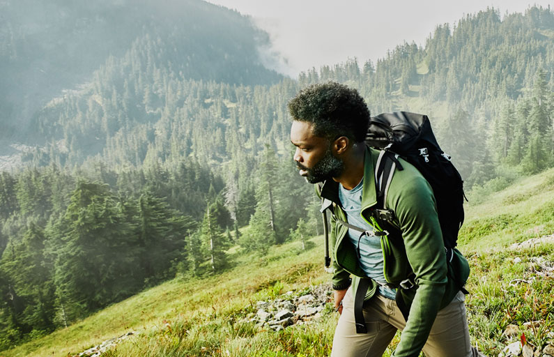 Man hiking atop a green mountain countryside